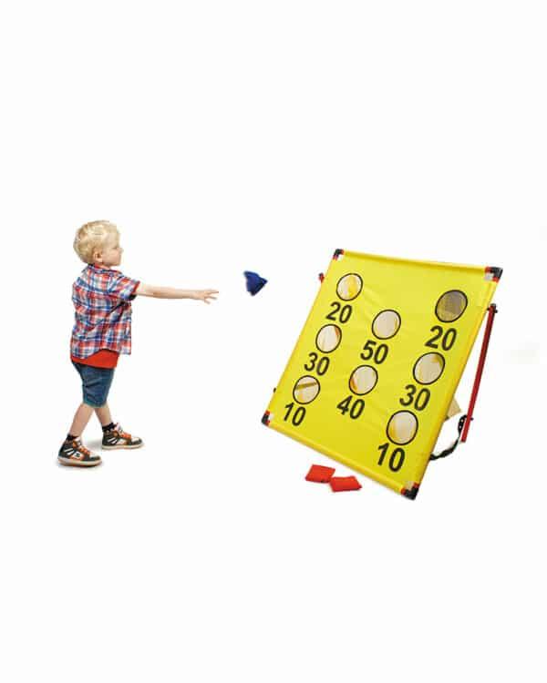 Boy throwing bean bag at target set