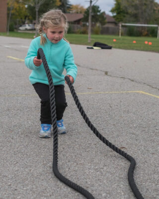 Girl using junior battle rope in school yard