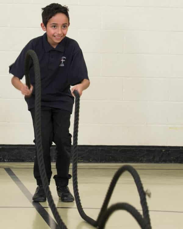 Boy doing battle rope exercise