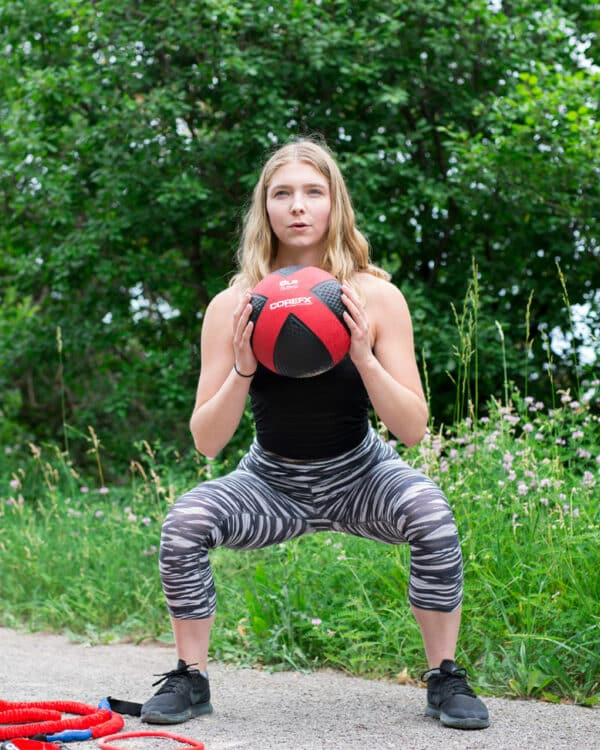 Woman doing squats with the COREFX Medicine Ball
