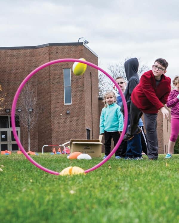 boy throwing football through hoop on base