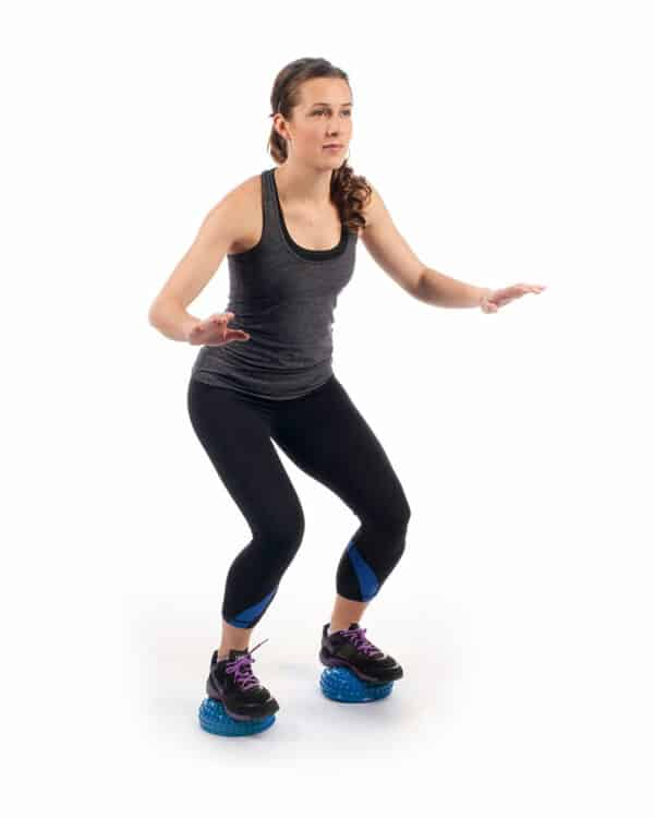 woman squatting using balance pods