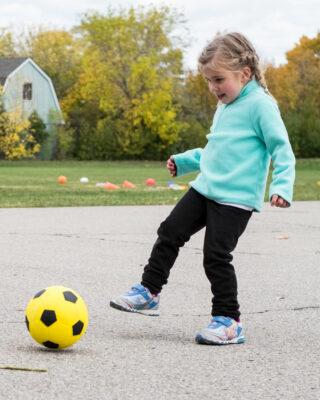 Girl Kicking Sponge Rubber Soccer Ball