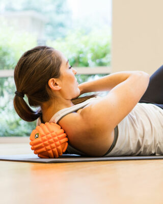 Woman using GRID Ball on shoulder