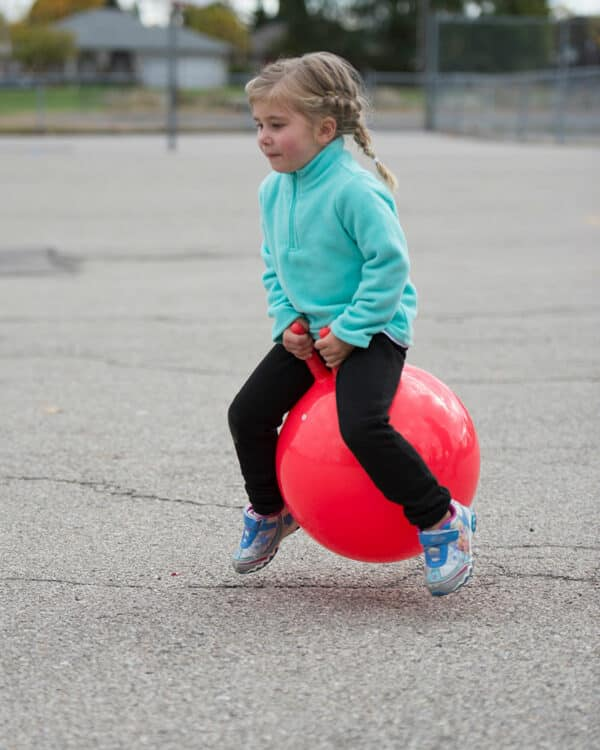 Girl bouncing on economy hop ball