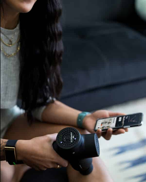Woman using Hypervolt Plus Bluetooth with app