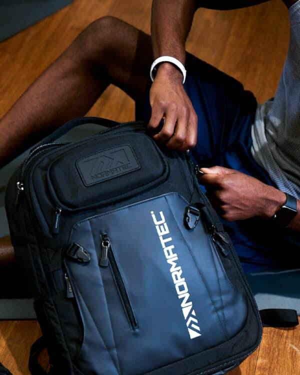 Man opening NormaTec Backpack