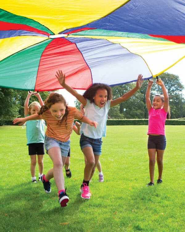girls running under multi-coloured parachute