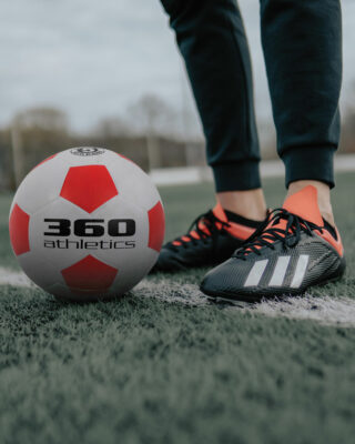 Rubber soccer ball on the field with soccer player