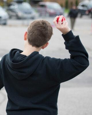 Boy throwing red practice tennis ball