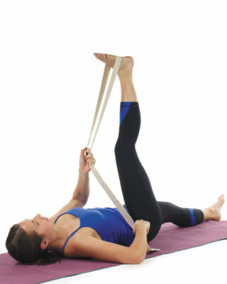 Woman stretching with yoga strap