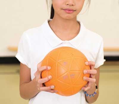 School girl holding trial play ball