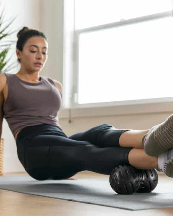 women using the universal massage ball on her calfs