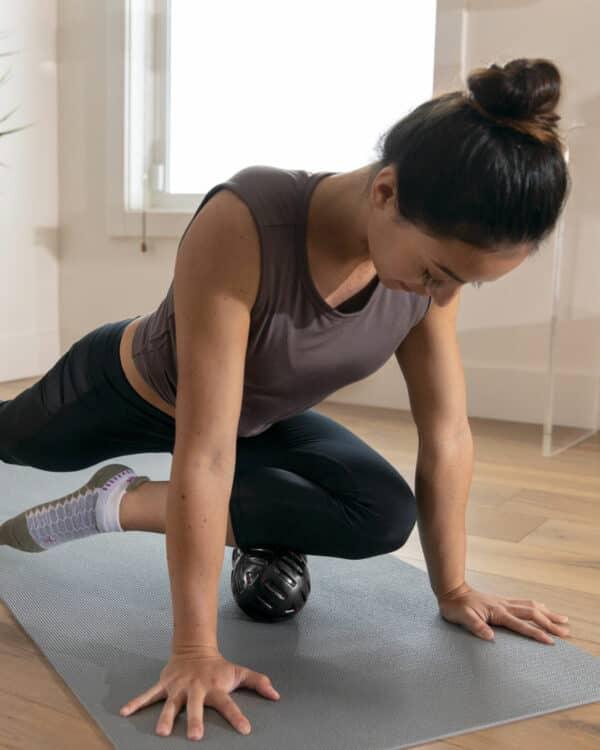 women using the universal massage ball on her shin